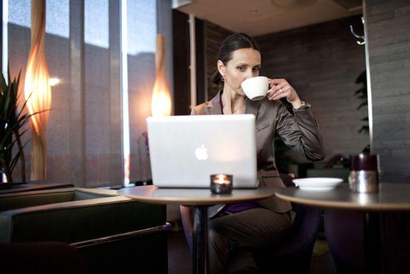 Uppmärksam kvinna dricker kaffe framför datorn på jobbet