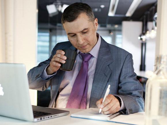kontorsklädd man noterar tips mot phishing framför datorn
